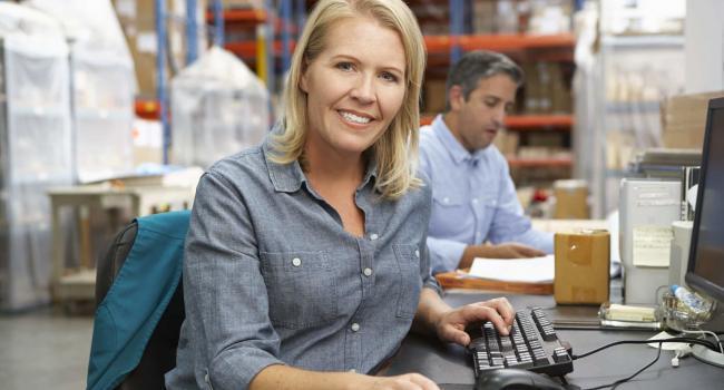19530814 - businesswoman working at desk in warehouse